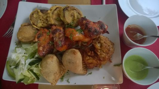 Indian Kitchen Apéro-Plate (geeignet für 2 bis 3 Personen) 2 Samosa, 4 Baingan Pakora, 2 Onion Bhaji, 4 Chicken Wings, Minz-Joghurtsauce, Chili-Tomatensauce, Garniert mit Salat)